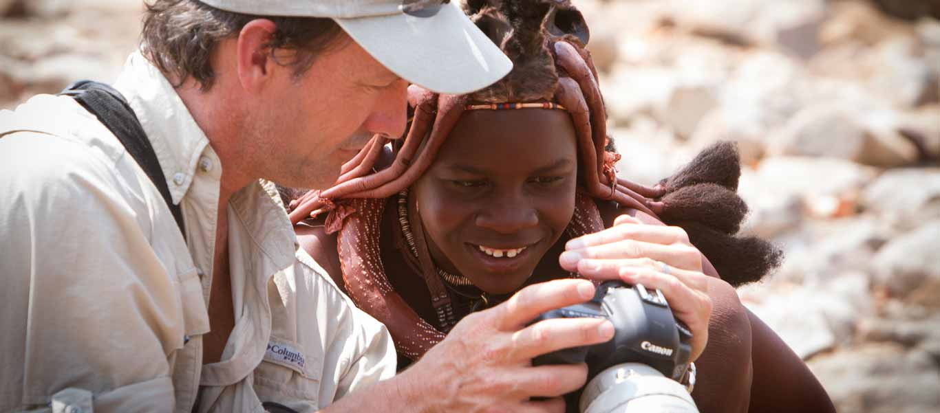 slide of expedition leader Jonathan Rossouw showing a camera to a nomadic Himba girl
