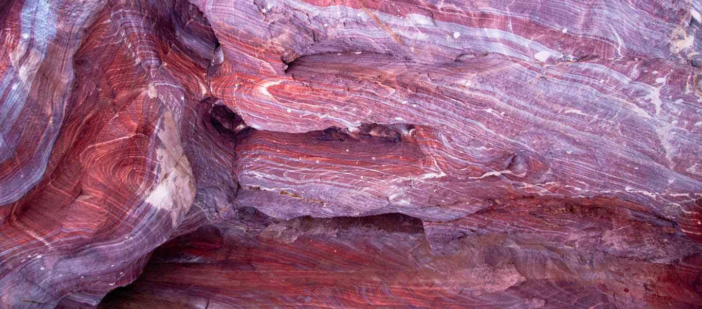 Petra tour image shows cliffs of solid red sandstone
