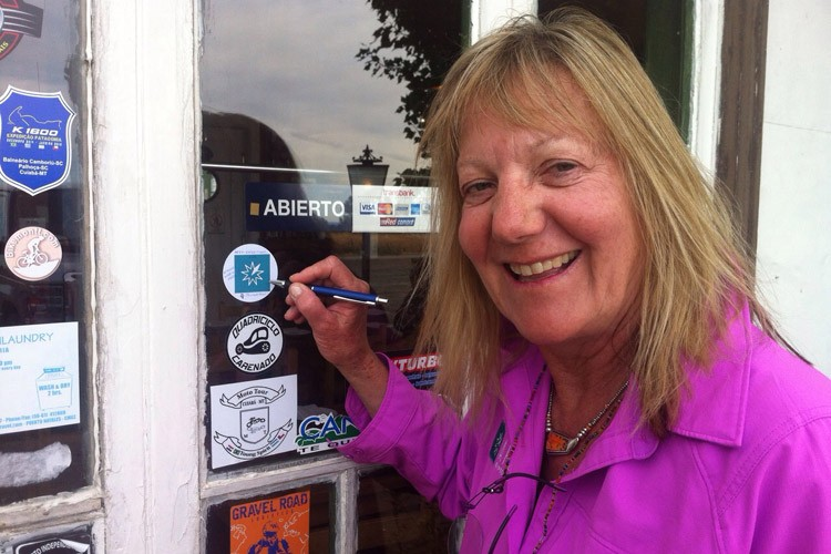 Patagonia tour photo of Shirley Metz signing an Apex Expeditions sticker on a door