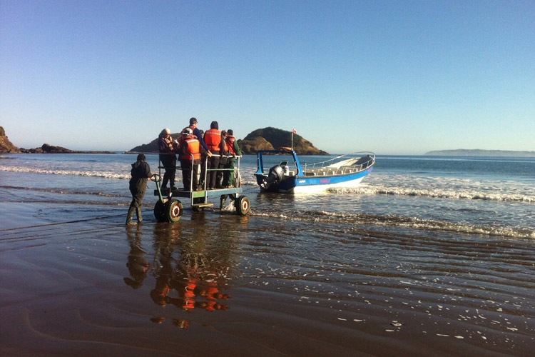 Chilean Patagonia tours slide shows travelers boarding boat on Chiloe Island