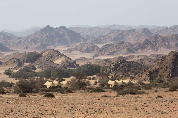 Namibia tour photo of Hoanib Skeleton Coast camp tents in mountain setting