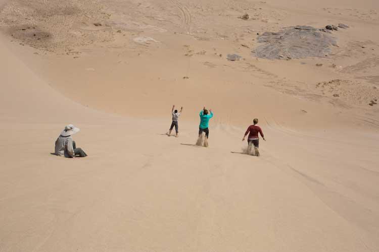 Namibia wildlife tour image of Apex Expeditions travelers sliding down dunes