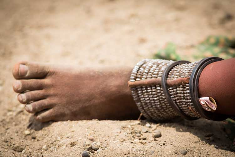 Namibia tour image of Himba woman wearing metal ankle jewelery