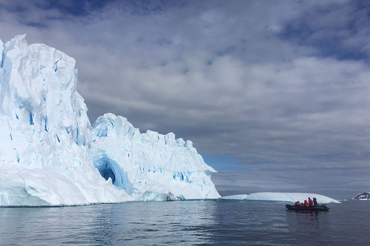 Antarctica ice with zodiac approaching iceberg on Antarctic Peninsula